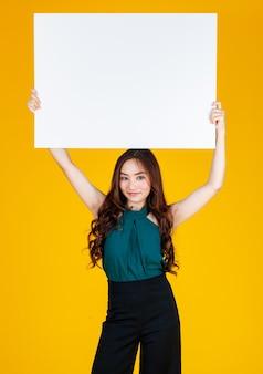 Capelli carini e piuttosto ricci bruna femmina asiatica che tiene un bordo bianco bianco sopra la testa con un gioioso per la pubblicità e lo scopo di uso banner, studio girato isolato su sfondo giallo brillante.