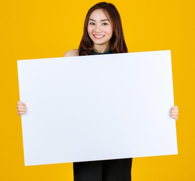 Capelli carini e piuttosto ricci bruna femmina asiatica che tiene il bordo bianco bianco posa alla telecamera con un gioioso per scopi pubblicitari e banner, studio girato isolato su sfondo giallo brillante.