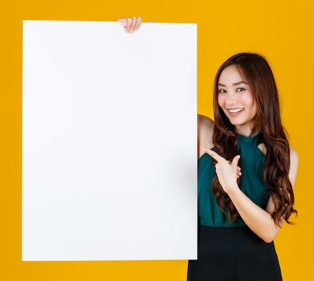 Capelli carini e piuttosto ricci bruna femmina asiatica che tiene il bordo bianco bianco posa alla macchina fotografica con uno scopo gioioso per la pubblicità e l'uso di banner, studio girato isolato su sfondo giallo brillante.