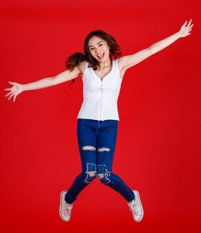 Carino e abbastanza scuro capelli donna asiatica sentirsi eccitato e saltare in aria con divertente e allegro per scopi di uso di banner e pubblicità, congelare stop motion isolato su sfondo rosso brillante.