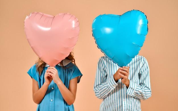 Una ragazza carina carina con riccioli in un vestito blu e un bravo ragazzo in una camicia stanno tenendo palloncini cuori di san valentino invece di una testa isolata