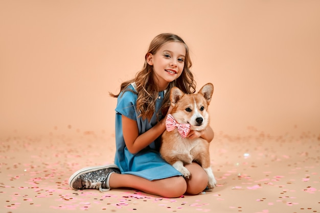 Carina bella ragazza con riccioli si siede sul pavimento con coriandoli e abbraccia un cane con un fiocco sul collo isolato