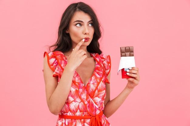 Donna abbastanza giovane sveglia che posa cioccolato isolato della tenuta della parete.