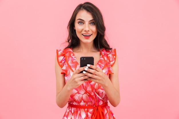 Carina piuttosto giovane donna in posa muro isolato utilizzando il telefono cellulare.