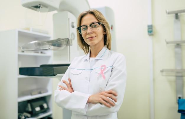 Medico donna professionale carino con nastro rosa, simbolo del mese di consapevolezza del cancro al seno.