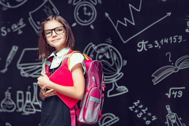 Allievo carino con gli occhiali che si prepara per andare a scuola con lo zaino e il libro in mano per tornare a scuola