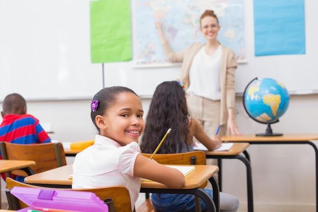 Carino alunni e insegnante in aula con il globo