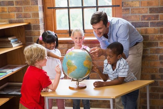 Alunni ed insegnante svegli che esaminano globo in biblioteca