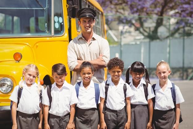 Alunni carini con il loro autista di scuolabus Foto Premium