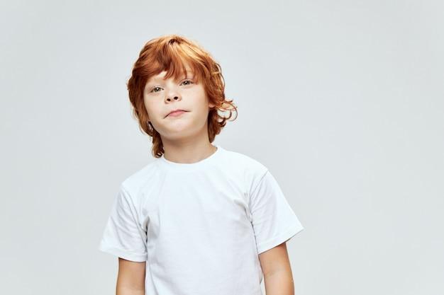 Il ragazzo dai capelli rossi sveglio in maglietta bianca sembra studio di vista ritagliata diritto