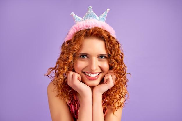 Ragazza carina principessa dai capelli rossi con riccioli in un vestito lucido e una corona sulla testa isolata su viola