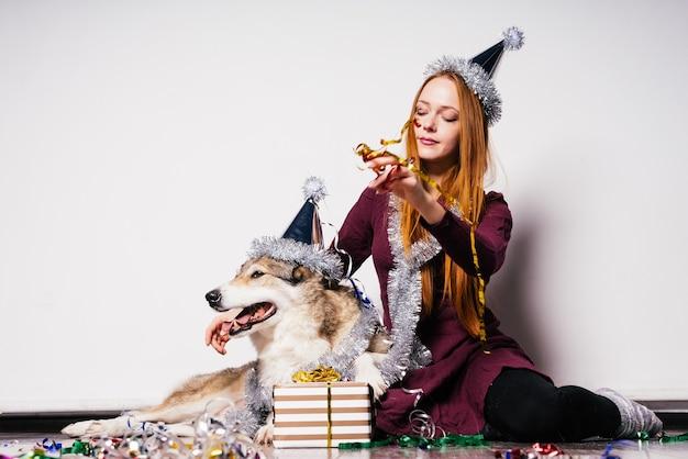 Carina ragazza dai capelli rossi si siede sul pavimento con il suo cane e festeggia il nuovo anno 2018