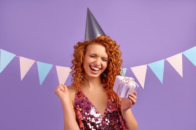 Una graziosa donna dai capelli rossi con riccioli in un vestito luccicante e un berretto da festa tiene in mano un regalo isolato su viola