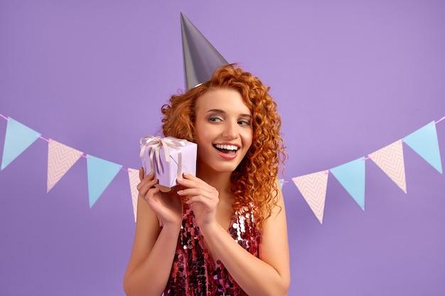 Carina donna dai capelli rossi con riccioli in un vestito lucido e un berretto da festa apre il suo regalo isolato su viola