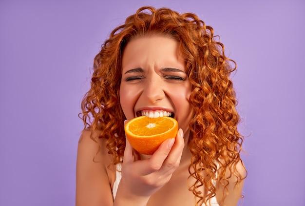 La ragazza carina rossa con i riccioli mangia l'arancia isolata sul muro viola. nutrizione appropriata. uno stile di vita sano.