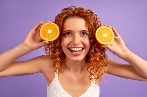 Ragazza carina rossa con riccioli che tengono metà delle arance isolate sulla parete viola. nutrizione appropriata. uno stile di vita sano.