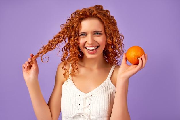Ragazza carina rossa con riccioli che tengono un'arancia isolata su un muro viola. nutrizione appropriata. uno stile di vita sano.
