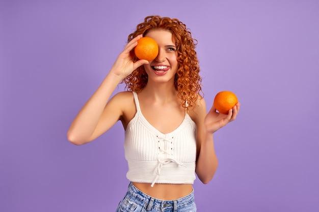 Ragazza carina rossa con riccioli che tengono arance isolate sulla parete viola. nutrizione appropriata. uno stile di vita sano.