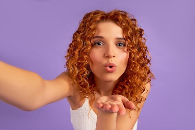 Carina ragazza rossa con riccioli fa un selfie e manda un bacio d'aria isolato su un muro viola.