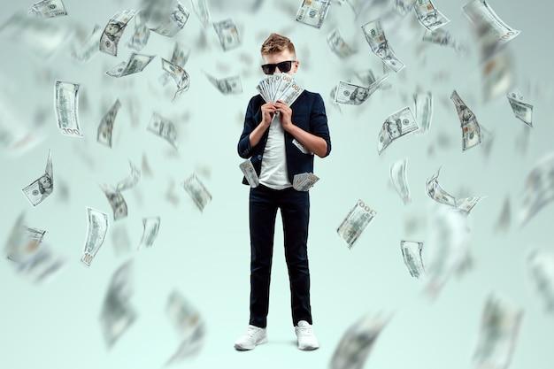 Un ragazzo carino e ricco con gli occhiali tiene in mano dollari e sa come fare soldi sullo sfondo delle banconote che cadono. pioggia di soldi, educazione finanziaria, giovane milionario, investimenti, prestiti, vincite