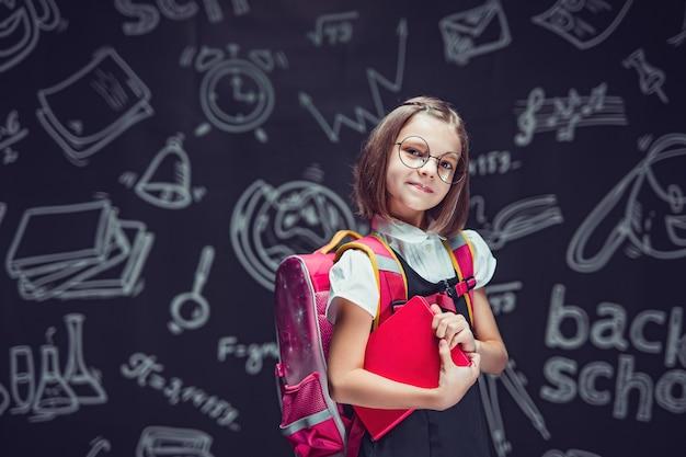 Studentessa carina con gli occhiali che si prepara per andare a scuola con lo zaino e il libro in mano per tornare a scuola