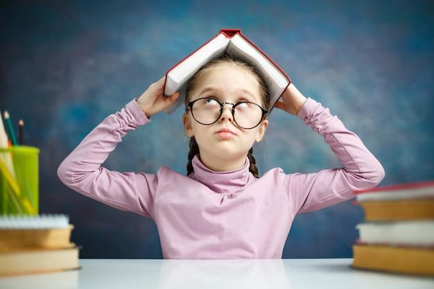 Testa sveglia della copertura di grido della scolara con il libro aperto