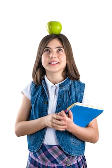 Studentessa carina in uniforme su priorità bassa bianca con la mela sulla sua testa.