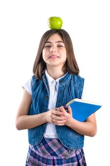 Studentessa carina in uniforme su bianco con la mela in testa
