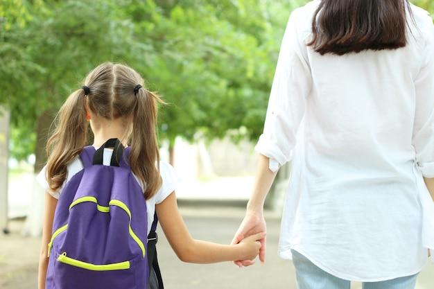 Studentessa carina con uno zaino scolastico nel cortile della scuola