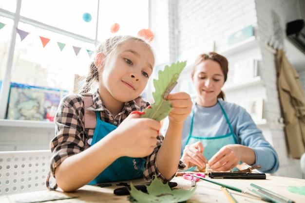 Studentessa carina con le forbici che tagliano la foglia di quercia secca mentre aiuta il suo insegnante con le decorazioni per le vacanze a lezione