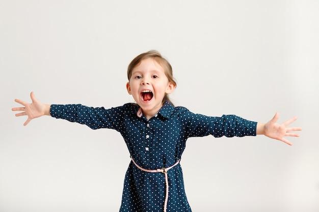 Carina ragazza urlante di 46 anni che indossa un vestito blu in piedi con la mano in direzioni diverse