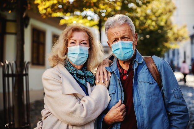 Carino coppia senior con maschere protettive in piedi nella parte vecchia della città.