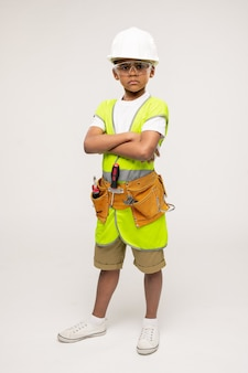Piccolo riparatore serio carino in abbigliamento casual, elmetto protettivo, occhiali protettivi e giacca uniforme che incrocia le braccia per il petto