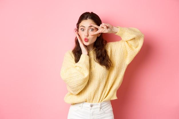 Ragazza carina sciocca che mostra baciare il viso e vsign sopra l'occhio che tocca la pelle del viso perfetta in piedi sorpreso contro il muro rosa