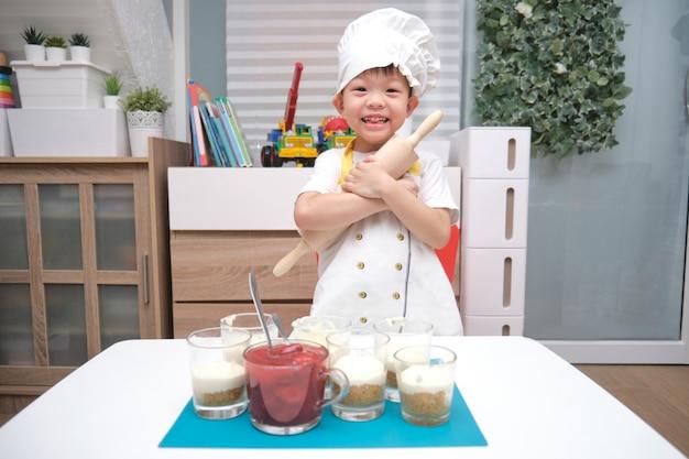 Asiatici sorridenti svegli 4 anni del bambino del ragazzo con un matterello divertendosi cucinando il dolce della fragola a casa, attività dell'interno di divertimento per il concetto di asilo