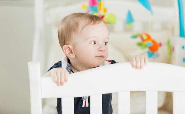 Simpatico neonato sorridente in piedi al suo letto