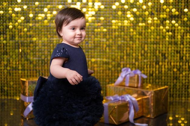 Bambina sorridente carina con scatole regalo su sfondo con paillettes dorate lucide, paillettes. Foto Premium
