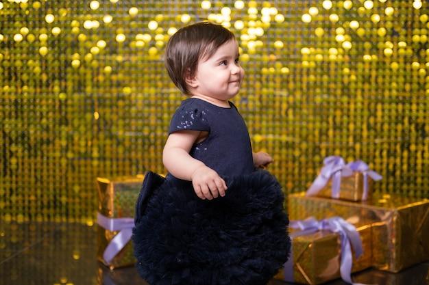 Bambina sorridente carina con scatole regalo su sfondo con paillettes di paillettes dorate lucide