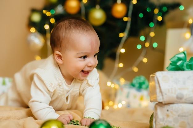 Il bambino sorridente sveglio è sdraiato sotto un albero di natale festivo e gioca con i regali