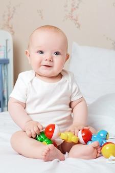 Simpatico bambino sorridente che ride e sorride con un giocattolo in mano ride sorriso buon umore giocattolo Foto Premium