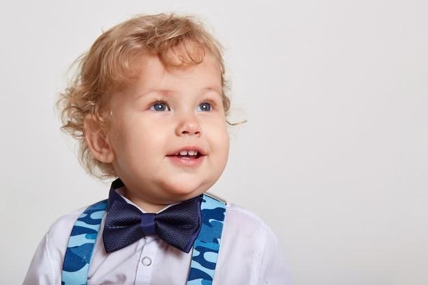 Ragazzo biondo sorridente sveglio del bambino del bambino in camicia bianca con il farfallino e le bretelle, che osserva da parte sopra lo spazio bianco