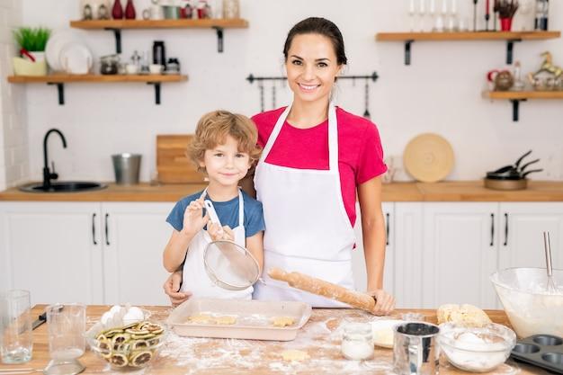 Ragazzo sorridente sveglio con il setaccio e sua madre con il mattarello in piedi dal tavolo della cucina mentre fanno i biscotti insieme