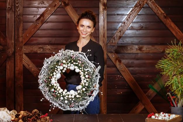 Progettista sorridente sveglio che mostra la corona dell'albero sempreverde di natale, giovane donna che tiene la corona di natale, corona di natale sulle mani femminili.