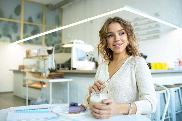 Carina donna sorridente in casualawear seduti a tavola in caffè, con cappuccino e gustosa torta di mirtilli in pausa