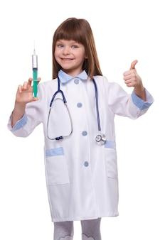 Medico sorridente sveglio della ragazza in siringa della tenuta dell'abito medico e che mostra il pollice su su fondo isolato bianco