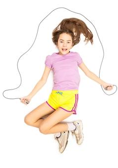 Carina ragazza sorridente sdraiata sul pavimento e fingendo di saltare con la corda