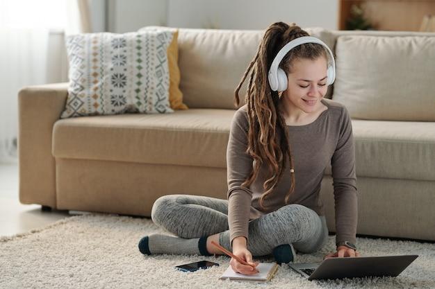 Ragazza sorridente sveglia con le cuffie che prendono appunti mentre sedendosi sul pavimento dal divano davanti al computer portatile