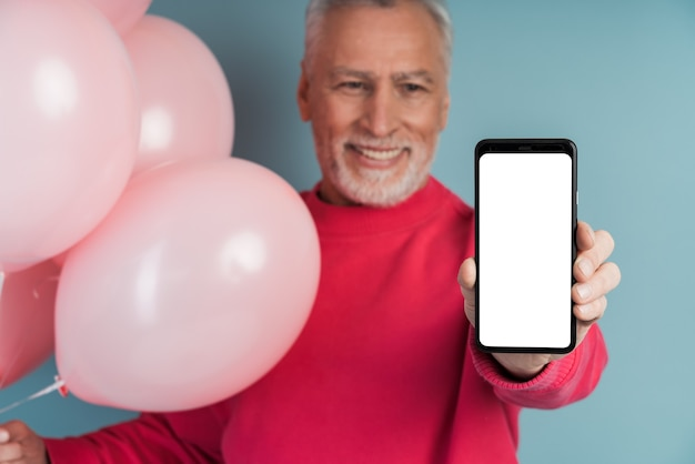 Il nonno carino e sorridente tiene un telefono, mostra una schermata bianca vuota