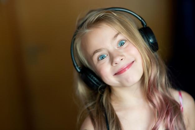 Carino sorridente bambina bambino in abito floreale e cuffie ascolta musica e balli su sfondo grigio