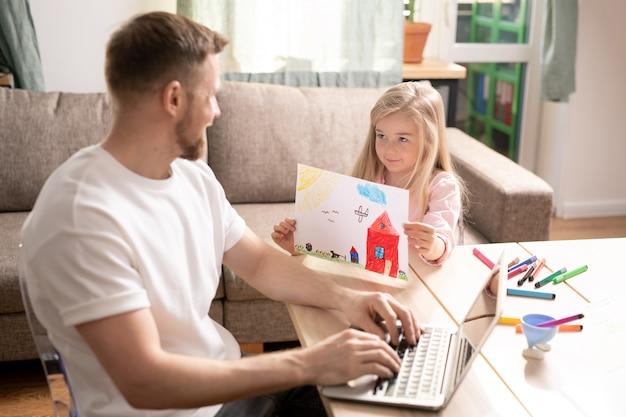 Piccola figlia sorridente sveglia che mostra l'immagine disegnata con le matite di colore a suo padre che digita sulla tastiera del computer portatile mentre lavora a distanza